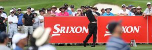 Golfer hits a tee shot in front of a large crowd